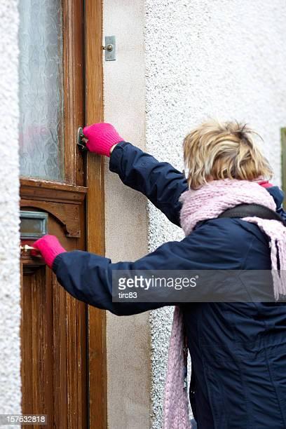 Mature blonde woman opening front door