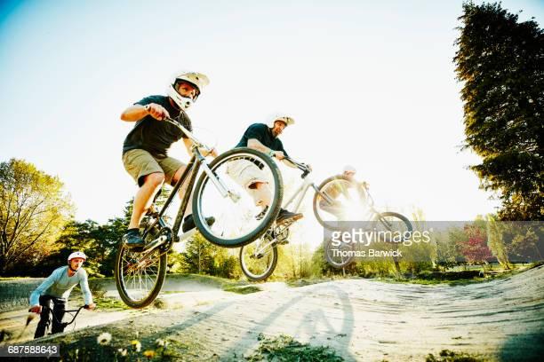 mature bmx rider racing over jump on bmx track - radsport wettbewerb stock-fotos und bilder