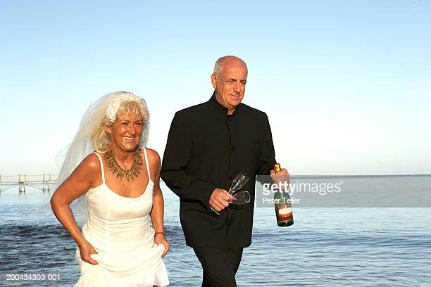 Mature bride and groom by sea, man carrying sparkling wine and glasses