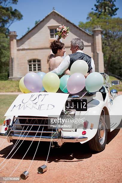 mature bride and groom riding in convertible - newlywed stock pictures, royalty-free photos & images