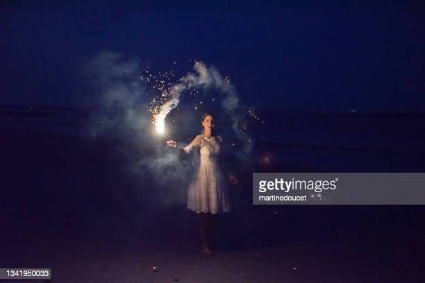 """mature bride lighting bengal fire on the beach at dusk. - """"martine doucet"""" or martinedoucet stock pictures, royalty-free photos & images"""
