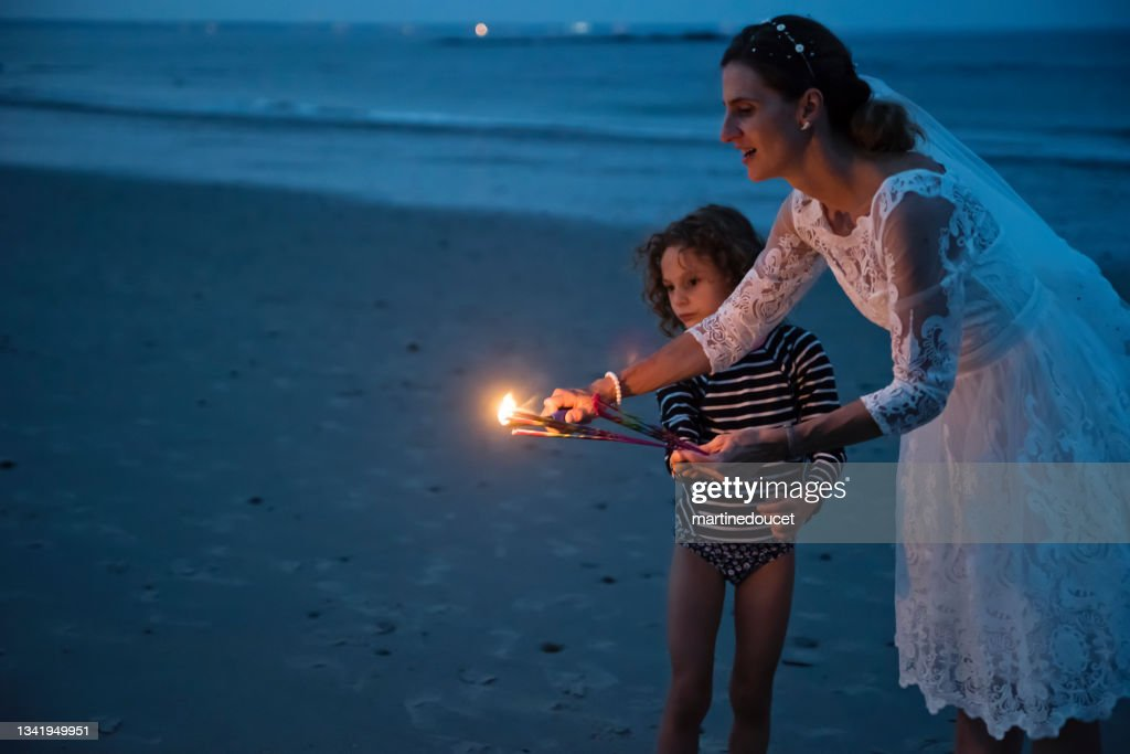 Mature bride lighting bengal fire with daughter on the beach at dusk. : Stock Photo