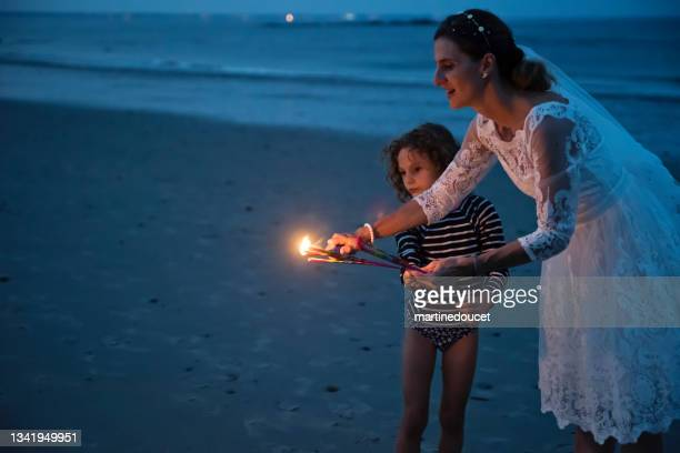 """mature bride lighting bengal fire with daughter on the beach at dusk. - """"martine doucet"""" or martinedoucet stock pictures, royalty-free photos & images"""