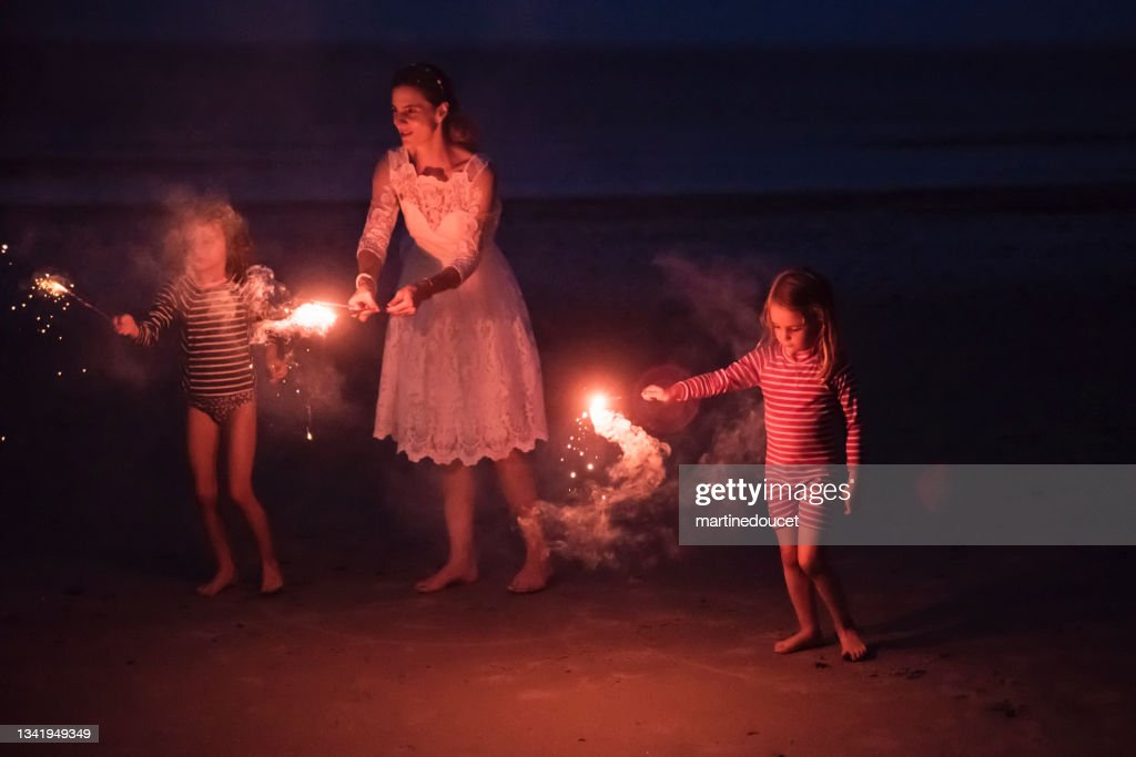 Mature bride lighting bengal fire with daughters on the beach at dusk. : Stock Photo