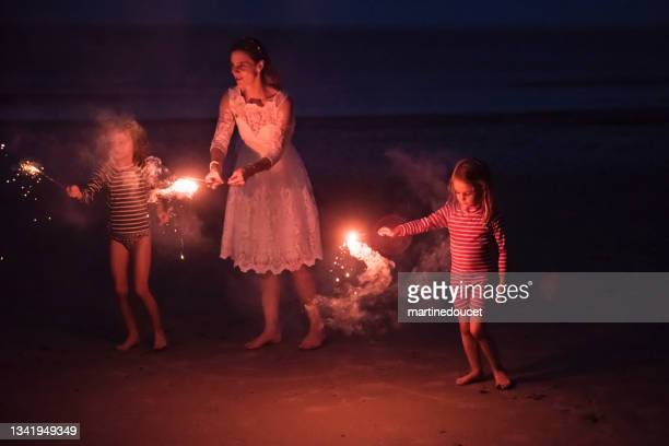 """mature bride lighting bengal fire with daughters on the beach at dusk. - """"martine doucet"""" or martinedoucet stock pictures, royalty-free photos & images"""