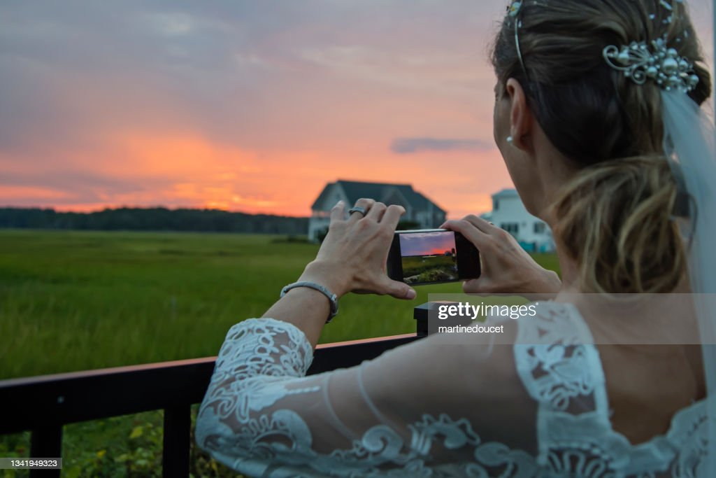 Mature bride photographing sunset in backyard. : Stock Photo