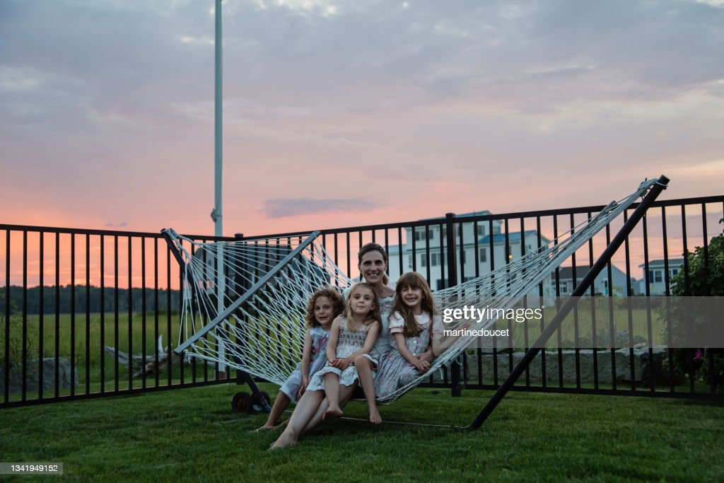Mature bride portrait with daughters in hammock at sunset. : Stock Photo