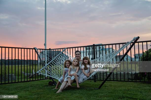 """mature bride portrait with daughters in hammock at sunset. - """"martine doucet"""" or martinedoucet stock pictures, royalty-free photos & images"""