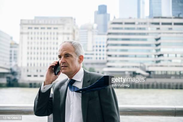 屋外のスマートフォンで話す成熟した英国のceo - ネクタイ ストックフォトと画像