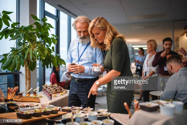mature business associates making gourmet food decisions - publicity event stock pictures, royalty-free photos & images
