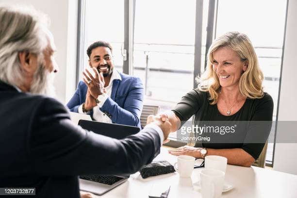 mature business associates shaking hands in agreement - applauding stock pictures, royalty-free photos & images