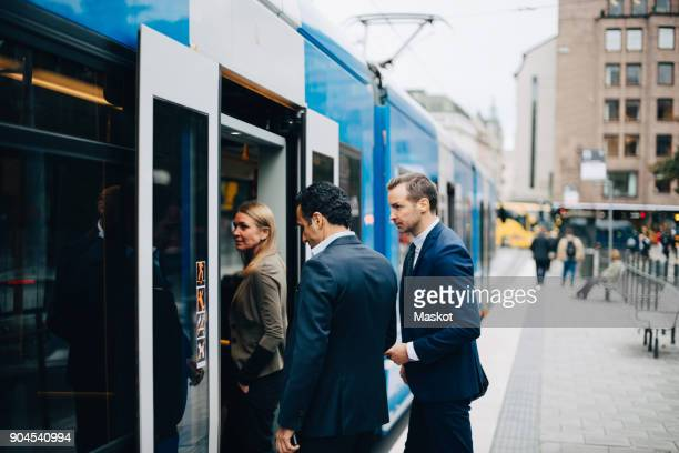 mature business colleagues entering cable car in city - tram stockfoto's en -beelden