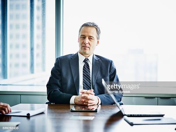 mature business executive at conference table - vestuário de trabalho formal - fotografias e filmes do acervo