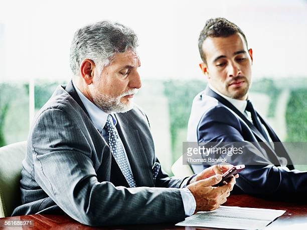 Mature business executive looking at smartphone