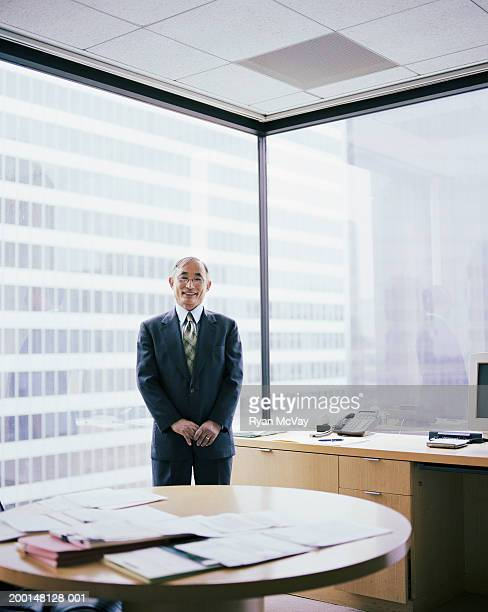 Mature business executive smiling, standing in office, portrait