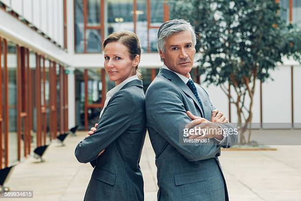 Mature business man and woman standing back to back looking at camera