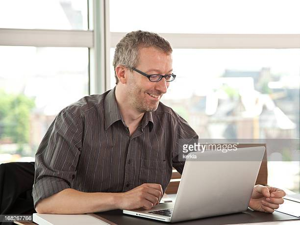 Mature business man smiling working at laptop