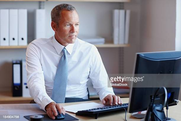 Mature business man using a computer in the office