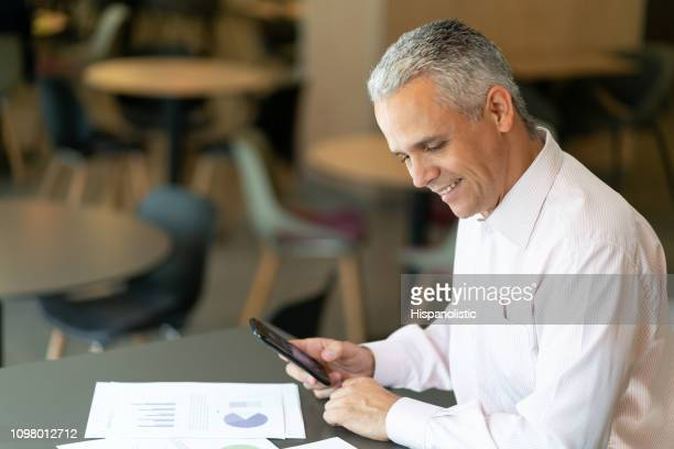 mature business man using his smartphone and looking at documents sitting at a hotel lounge smiling - hispanolistic stock photos and pictures