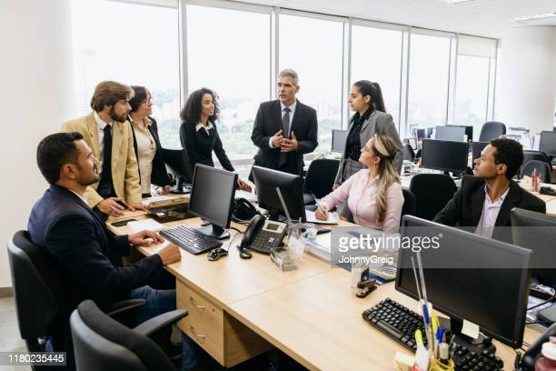 mature business manager explaining to colleagues in meeting - 30 39 years stock pictures, royalty-free photos & images