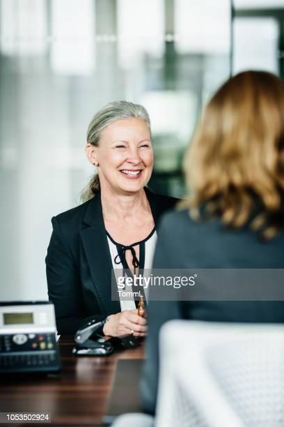 ausgereifte business manager lächelnd, im gespräch mit kollegen - vertikal stock-fotos und bilder