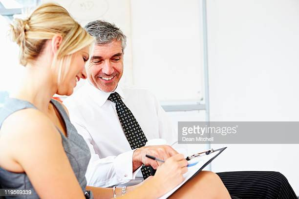 mature business mentor helping female with reports