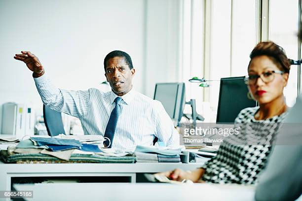 Mature business owner leading meeting