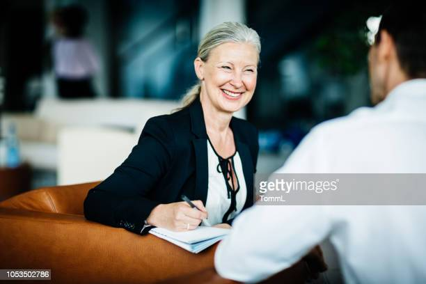 mature business owner pleased while talking to employee - honesty stock pictures, royalty-free photos & images