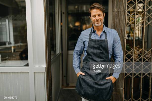 mature business owner standing in front of his bakery shop - hands in pockets stock pictures, royalty-free photos & images