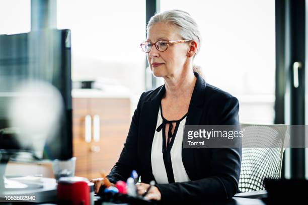 mature business owner working at computer - business finance and industry stock pictures, royalty-free photos & images