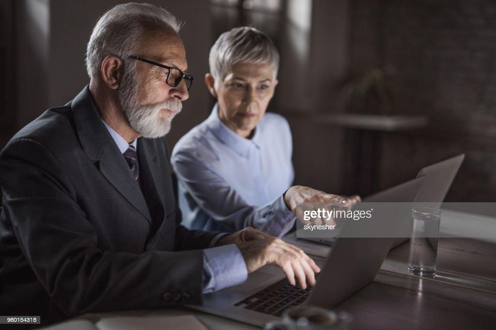 Reife Geschäftsleute arbeiten gemeinsam an einem Laptop im Büro. : Stock-Foto