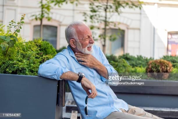 成熟したビジネスマンは、通りで窒息を持っています - 喉が詰まる ストックフォトと画像