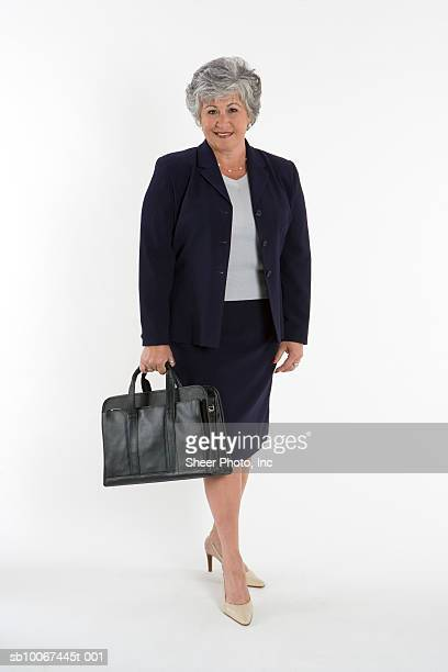 mature business woman holding purse - older women in short skirts stock pictures, royalty-free photos & images
