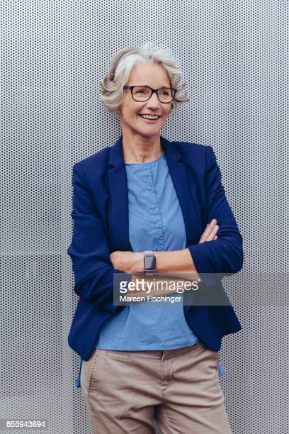 Mature business woman leaning at wall outside office building