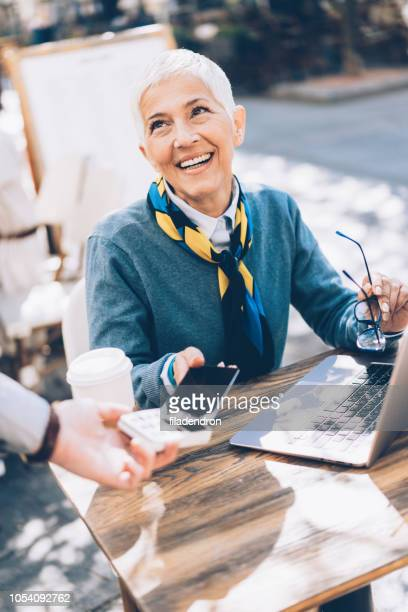 Mature business woman paying contactless with smartphone