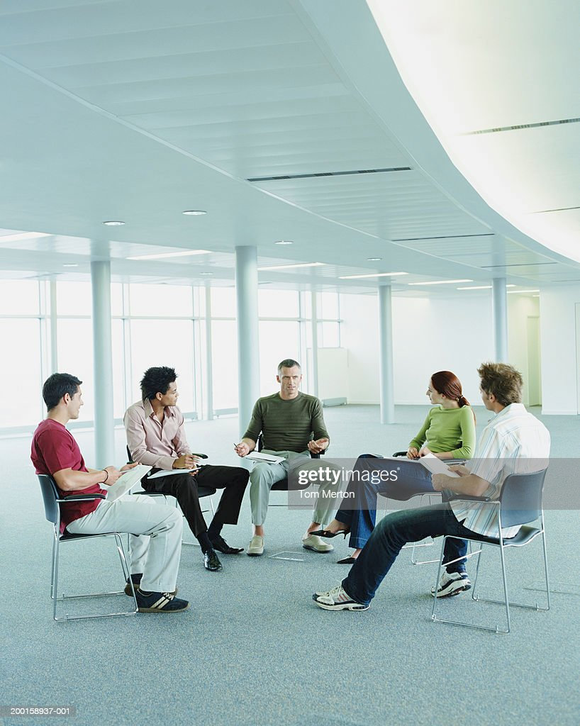 Mature businessman addressing colleagues in empty office : Stock Photo
