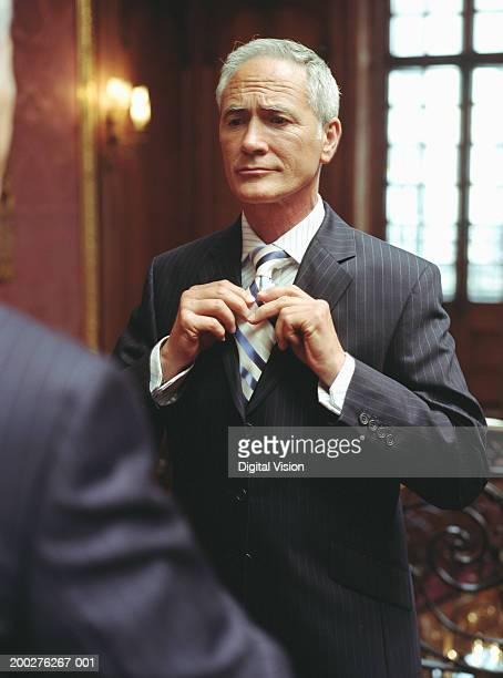 mature businessman adjusting tie, reflection in mirror - adjusting necktie stock pictures, royalty-free photos & images