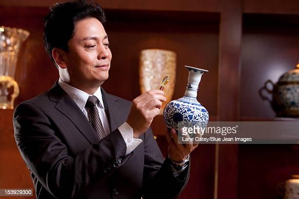 Mature businessman admiring an antique Chinese vase