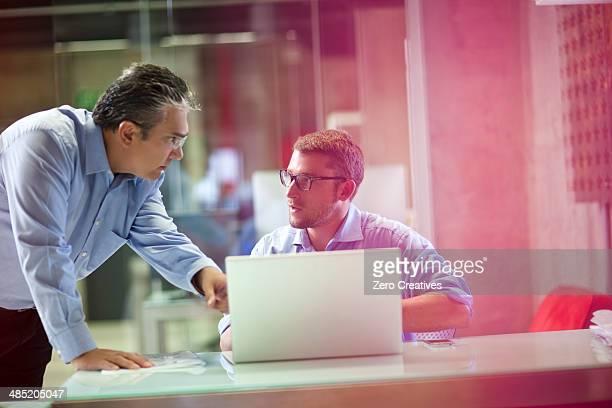 Mature businessman advising male office worker