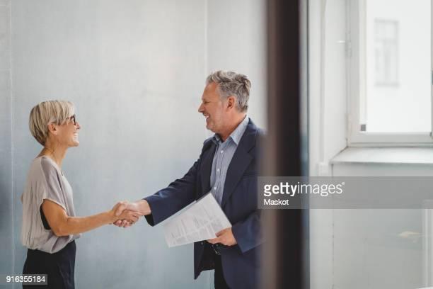 mature businessman and businesswoman shaking hands in new office - grüßen stock-fotos und bilder