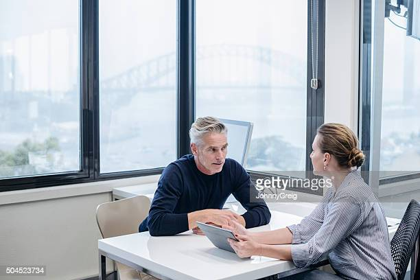 Mature businessman and female colleague in office with tablet