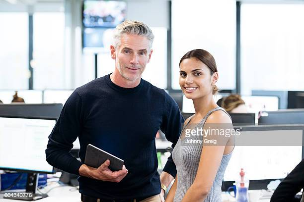 Mature businessman and young Aboriginal Australian woman in office