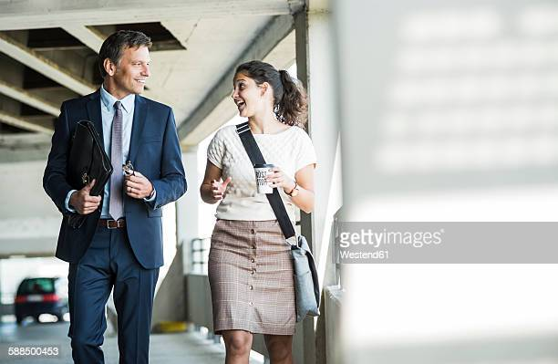 Mature businessman and young colleague walking in parking garage, talking