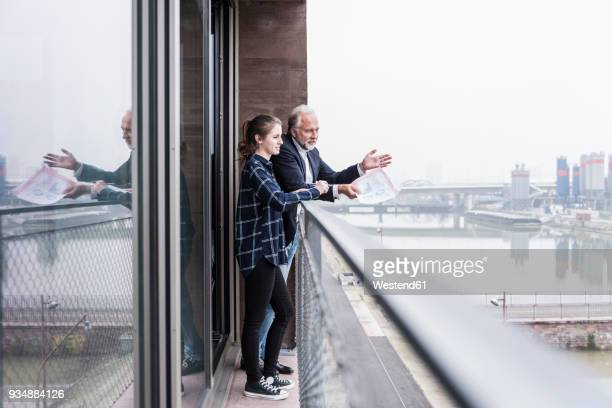 Mature businessman and young woman talking on balcony