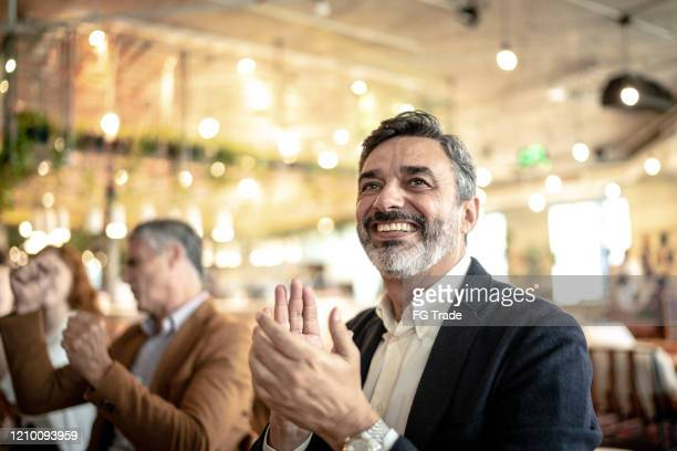 mature businessman applauding at business meeting - awards ceremony stock pictures, royalty-free photos & images