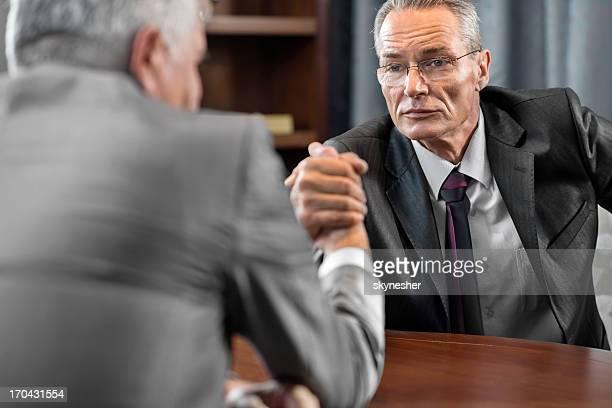 Mature businessman arm wrestling