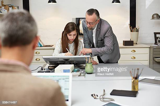 Mature businessman assisting intern on screen