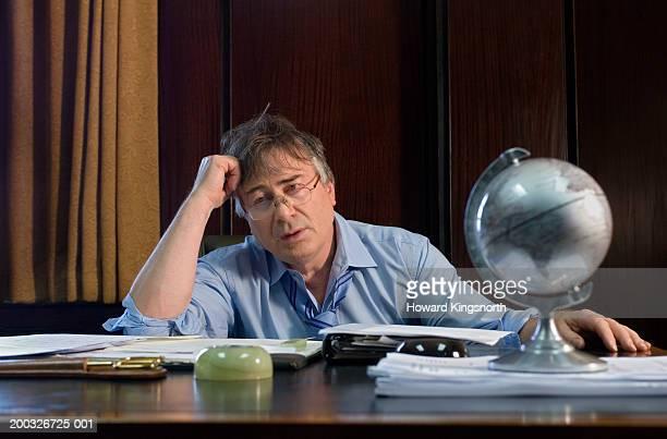 Mature businessman at desk, resting head on hand