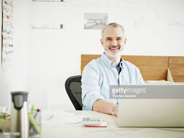 Mature businessman at laptop in startup office