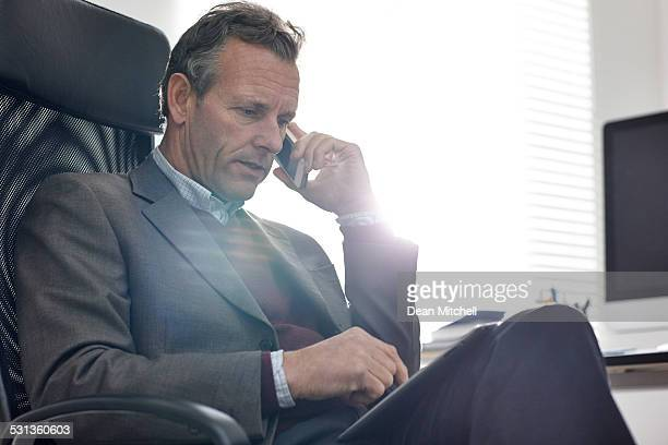 Mature businessman at office talking on phone